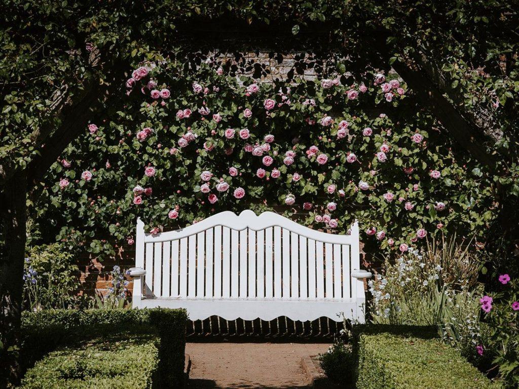 weiße Sitzbank aus Holz im Garten