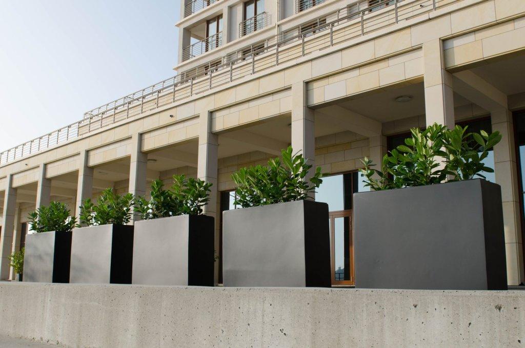 """Das beliebte Trennelement """"Elemento"""" aus Fiberglas in Anthrazit, im Hintergrund die beeindruckende Fassade des Hotels."""